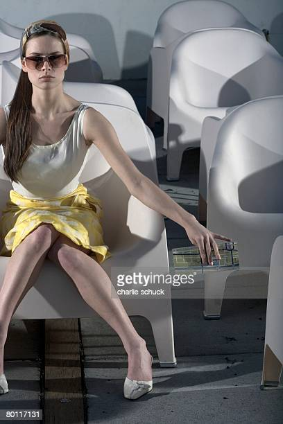 Woman with sunglasses sitting in chair