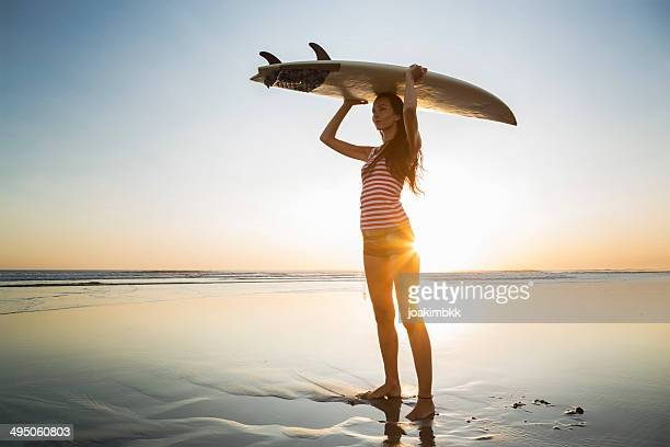 Woman with surf board to conquer the sea
