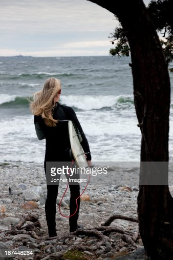 Woman with surfboard on beach : Stock Photo