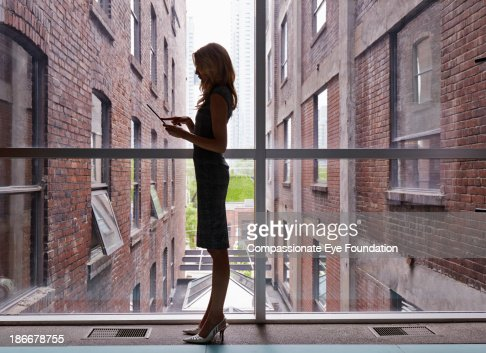 Woman with tablet computer standing against window : Stock Photo