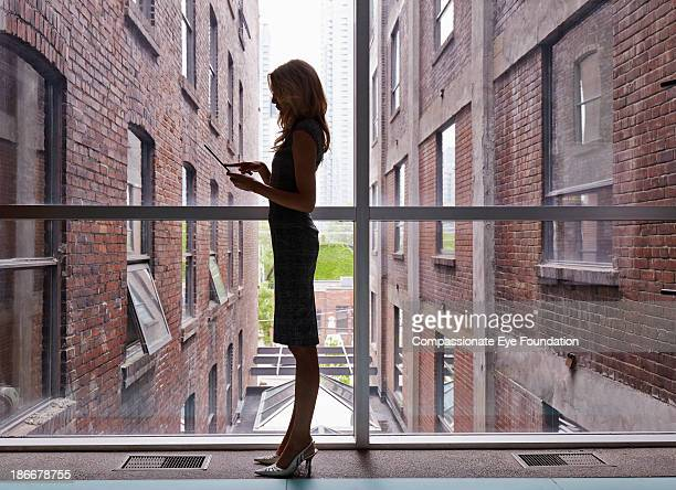 Woman with tablet computer standing against window