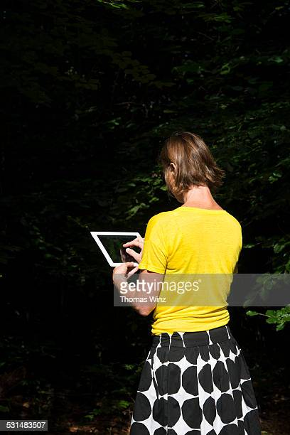 Woman with tablet in the woods