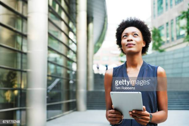 Woman with tablet looking up