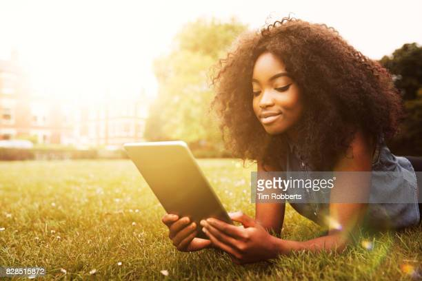 Woman with tablet on grass