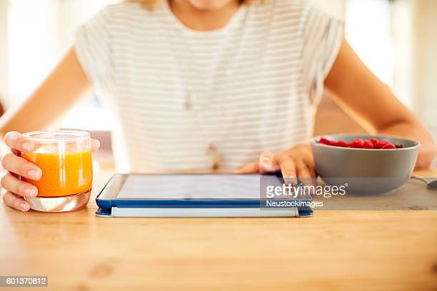 Woman with tablet PC and orange juice at table