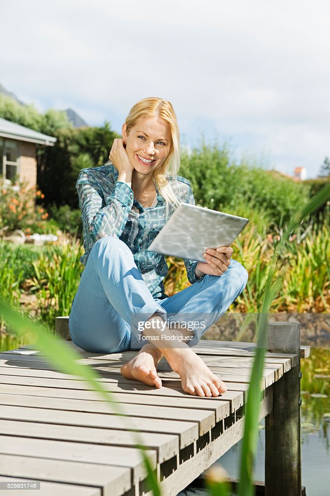 Woman with tablet pc on jetty : Stock-Foto