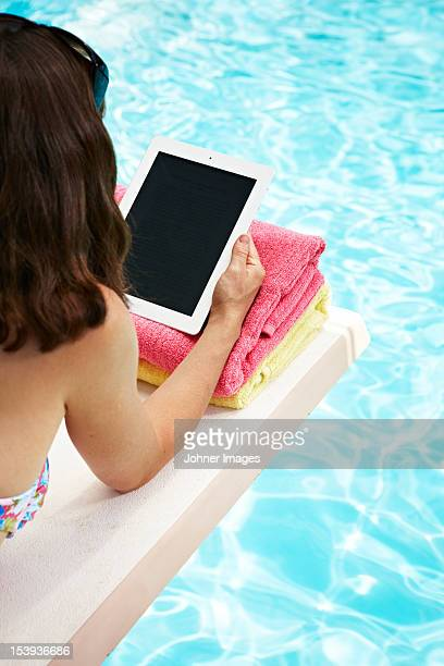 Woman with tablet pc on pool raft