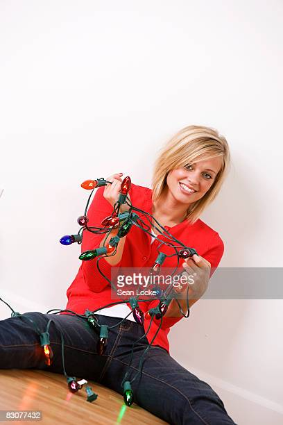 Woman with tangled string of Christmas lights
