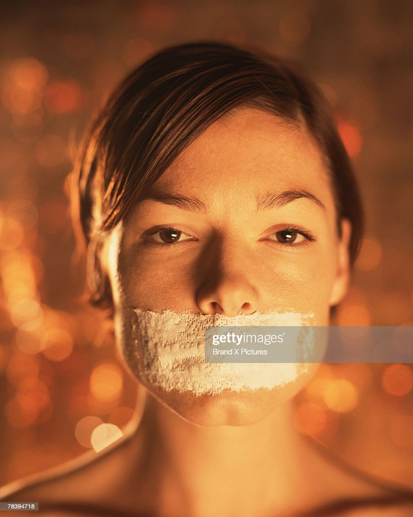 Woman with tape on mouth : Stock Photo
