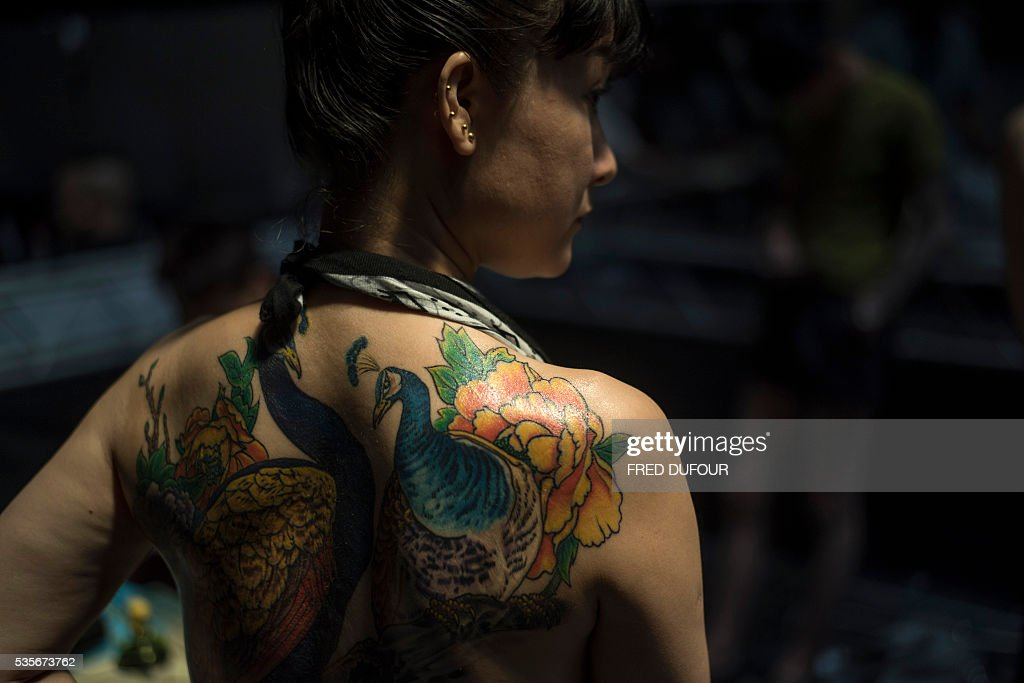 A woman with tattoo attends the Langfang International Tattoo show, in Hebei province, on May 29, 2016. / AFP / FRED