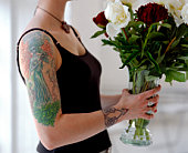 Woman with tattooed arm carrying vase of flowers