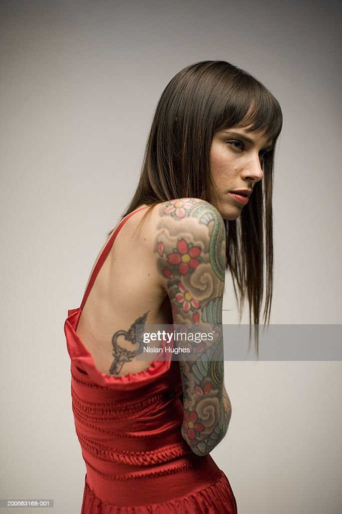 Woman with tattooed arm, looking away : Stock Photo