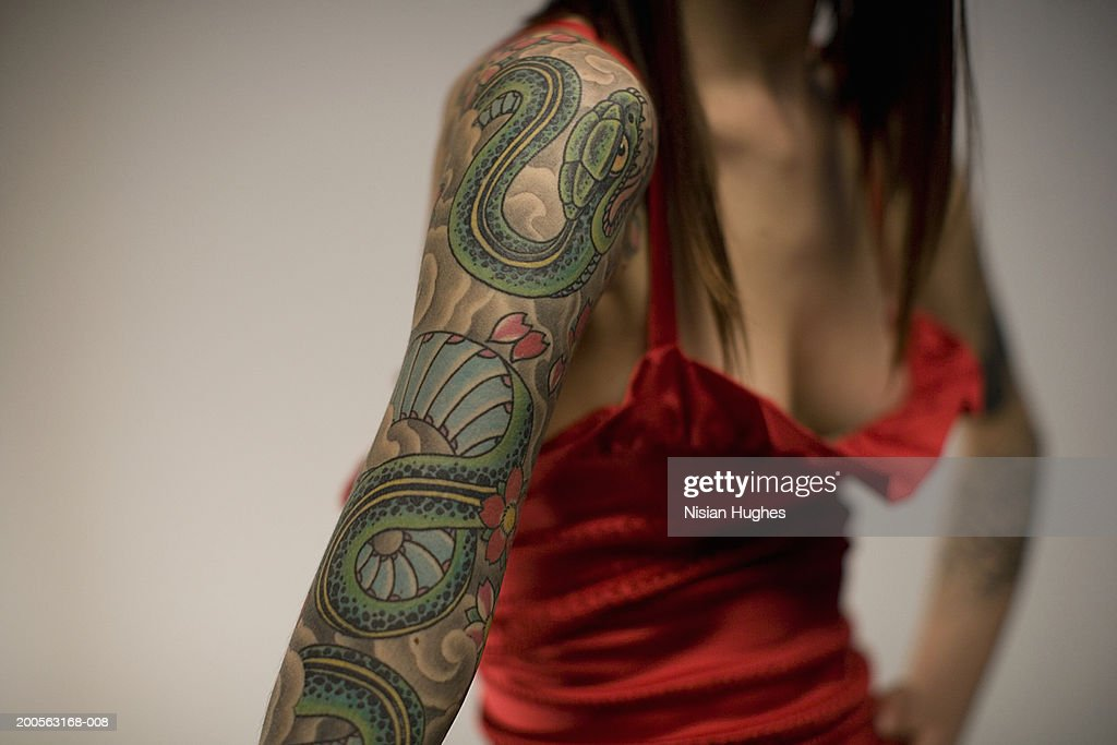 Woman with tattooed arm, mid section : Stock Photo