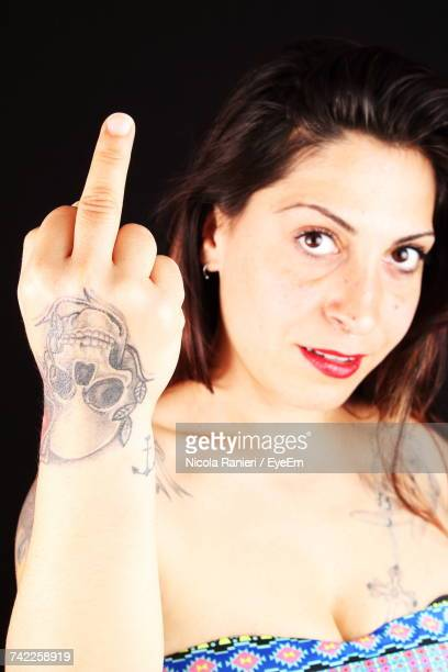 Woman With Tattooed Hand Showing Obscene Gesture Against Black Background