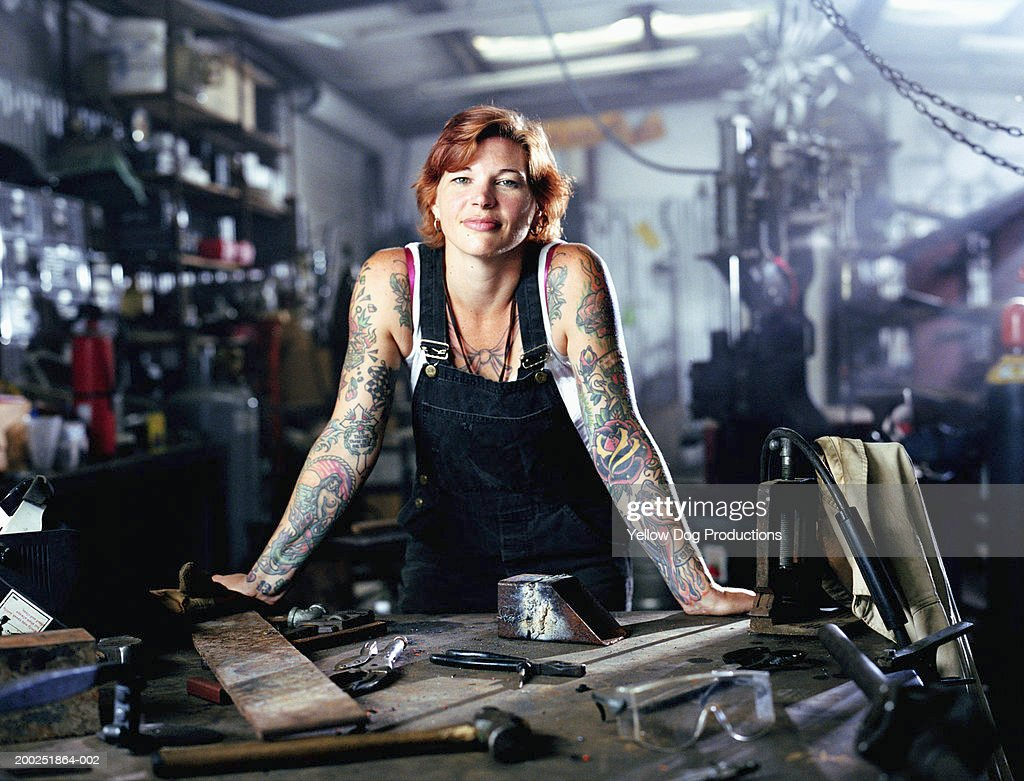 Woman with tattoos in both arms in factory, portrait : Stock Photo