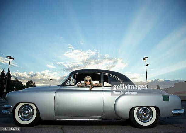 Woman with tattoos leaning out window of 1951 Chevy