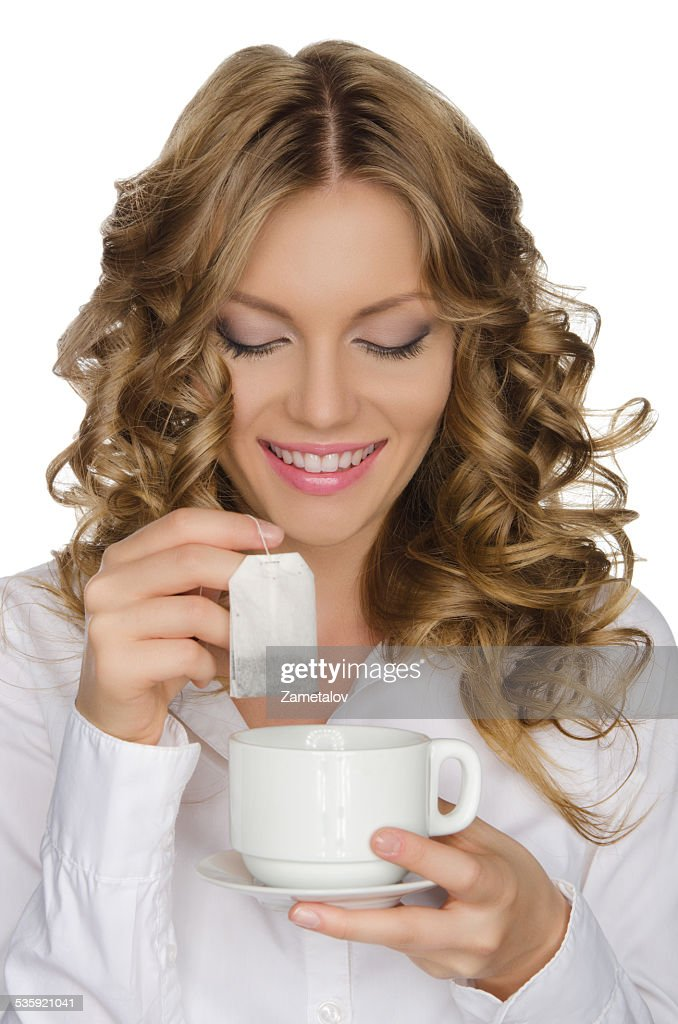 woman with tea bag looks into cup : Stock Photo