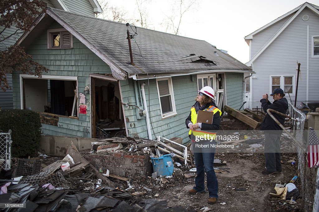 A woman with the Army Corps of Engineers and a representative from FEMA document a destroyed home November 28, 2012 in a residential area of New Dorp Beach in the Staten Island borough of New York City. Parts of the New Dorp Beach neighborhood were submerged under 10 feet of water during the height of Superstorm Sandy one month ago.