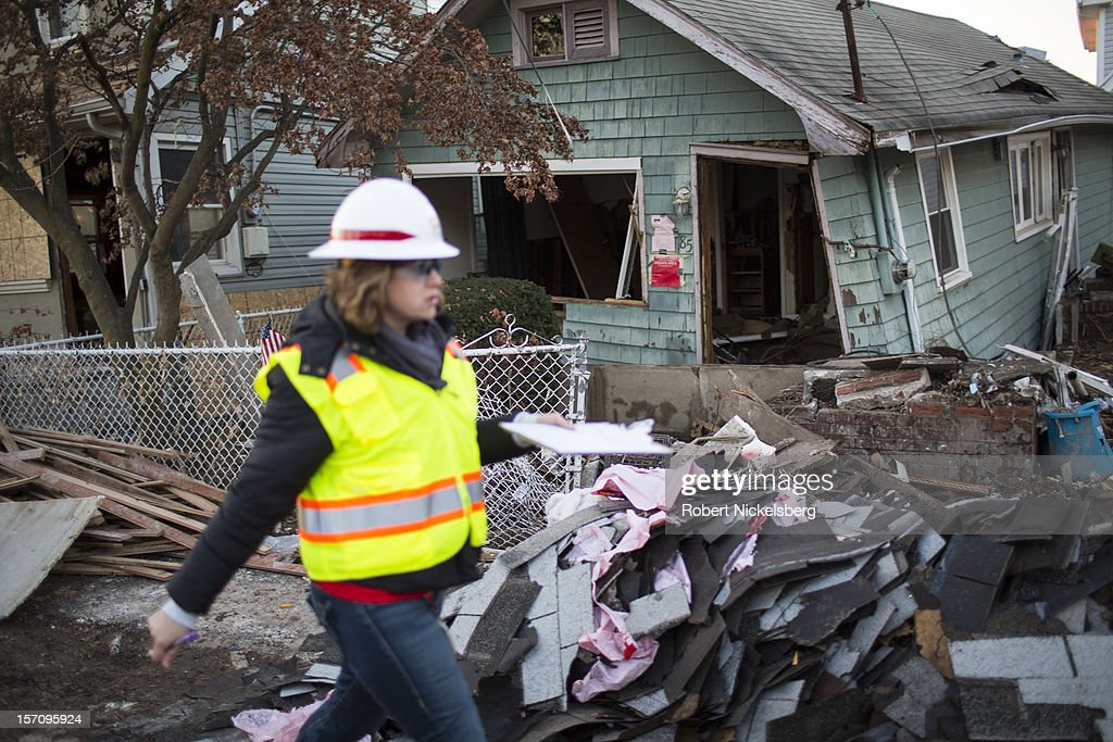 A woman with the Army Corps of Engineers documents a destroyed home November 28, 2012 in a residential area of New Dorp Beach in the Staten Island borough of New York City. Parts of the New Dorp Beach neighborhood were submerged under 10 feet of water during the height of Superstorm Sandy one month ago.