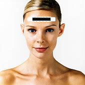 Woman with thermometer strip on forehead, close-up, portrait