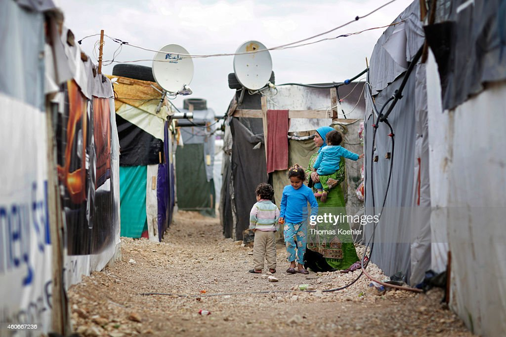 Woman with three children in an informal tented settlement of Syrian refugees on December 09 2014 in Zahle Lebanon The ongoing civil war in Syria...