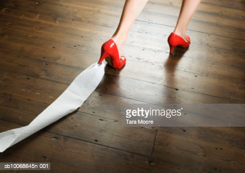 Woman with toilet paper stuck to shoe, low section