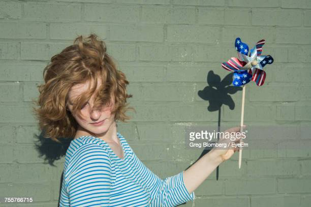 Woman With Tousled Hair Holding American Flag Pinwheel Toy By Green Wall
