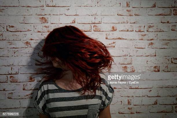 Woman With Tousled Hair Standing Against Brick Wall