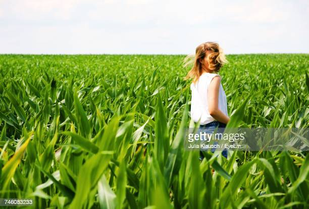 Woman With Tousled Hair Standing Amidst Crops Growing On Field