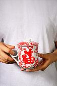 Woman with traditional Chinese tea mug