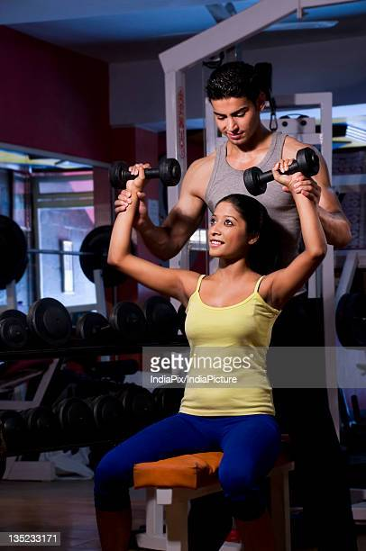 Woman with trainer at the gym