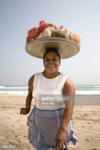 Woman with Tray of Shells on Head at Beach