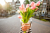 Woman giving a beautiful bouquet of pink tulips standing outdoors in Amsterdam city