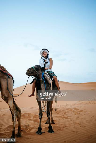 Woman with turban riding a camel in the desert