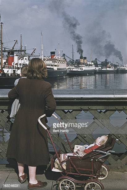 A woman with two children stops to look at shipping in a harbour Belfast Northern Ireland June 1955 Original publication Picture Post 7825 Belfast...