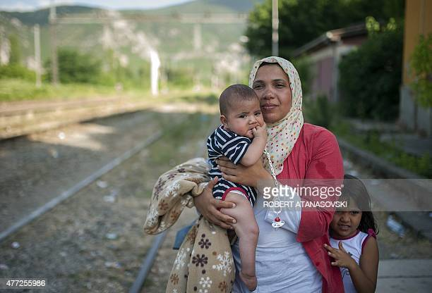 A woman with two children tries to board a train in Demir Kapija on her way to the Serbian border on June 15 2015 They were walking and crossing the...