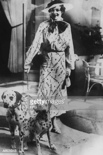 Woman with two dalmatians wearing patterned dress (B&W) : Bildbanksbilder