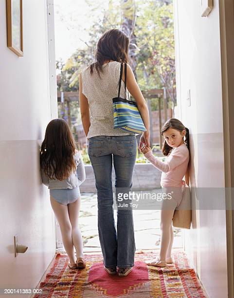 Woman with two girls (4-6) in ballet costumes in doorway