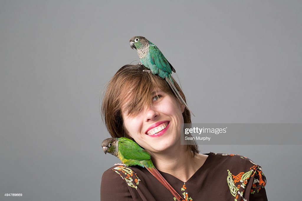 Woman with two Green-cheeked Parakeets : Stock Photo