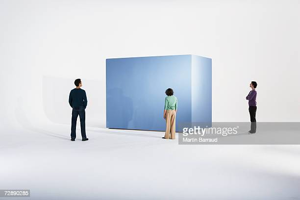 Woman with two men beside giant box