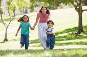 Woman with two young children running outdoors smiling having fun