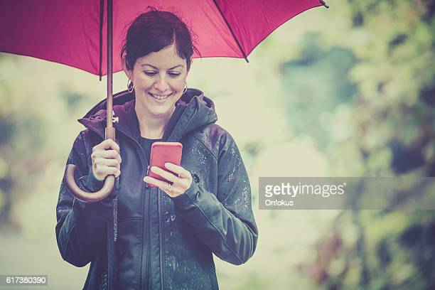 Woman with Umbrella and Smart Phone
