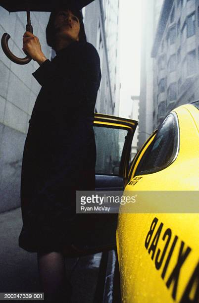 Woman with umbrella exiting taxi in rainy street