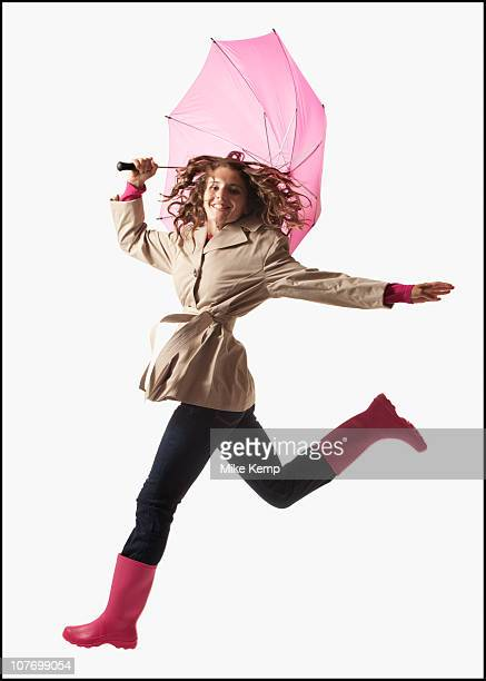 Woman with umbrella jumping on white background