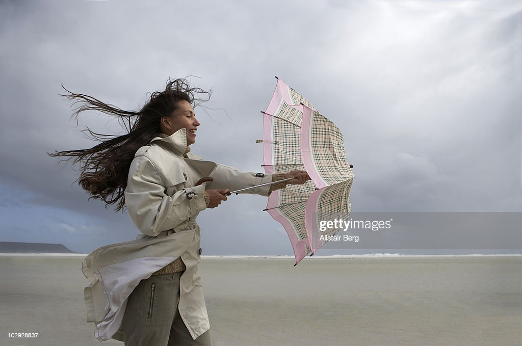 Woman with umbrella on windy beach