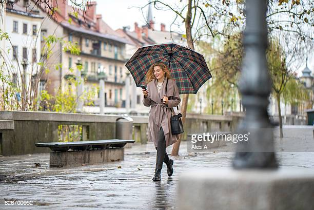 Woman with umbrella walking down the street
