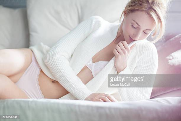 Woman with underwear and cardigan on a sofa