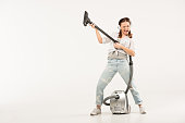Young woman in headphones holding vacuum cleaner and pretending she playing electric guitar