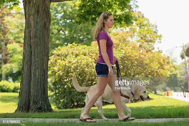 Woman with visual impairment walking with her service dog