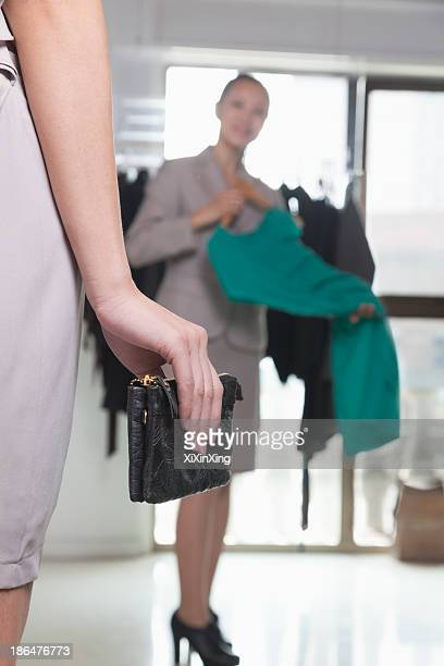 Woman with wallet at fashion store, close-up